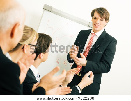 Business team applauding after a successful business presentation (selective focus only on the presenter!) - stock photo