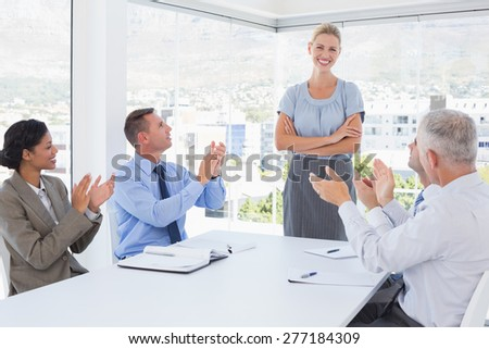 Business team applauding their colleague in the office - stock photo