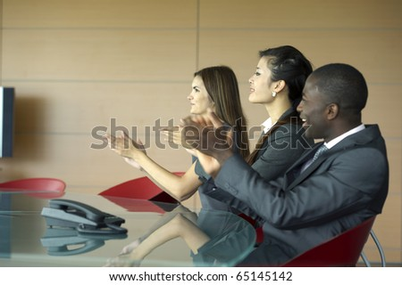 Business team applauding while at a meeting
