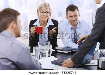 Business team at discussion, looking at laptop, businesswoman drinking coffee looking at screen, talking. - stock photo