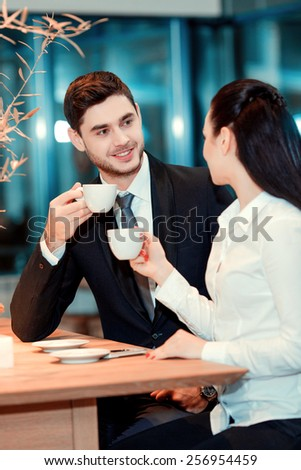 Business team at lunch. Handsome young man in suit and beautiful woman drinking coffee and speaking while sitting at the restaurant  - stock photo