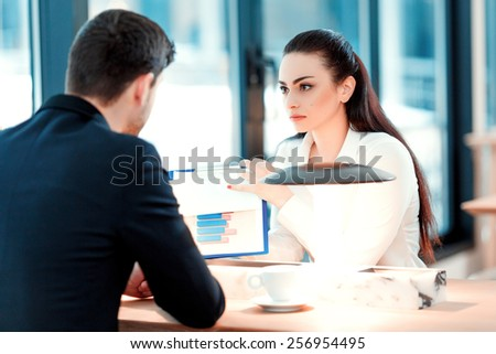 Business team at lunch. Image of beautiful young woman in formalwear pointing at clipboard with analytics while sitting at the restaurant with her colleague  - stock photo