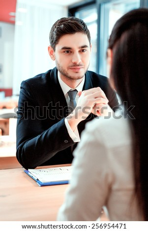 Business team at meeting. Handsome young man speaking with his female colleague while sitting at the restaurant  - stock photo