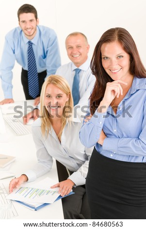 Business team attractive businesswoman with happy colleagues working on charts - stock photo
