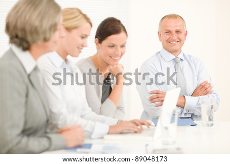 Business team attractive businesswomen with happy colleagues working around table - stock photo