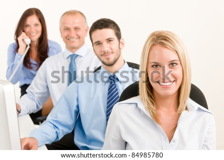 Business team attractive woman sit in line behind computer table - stock photo