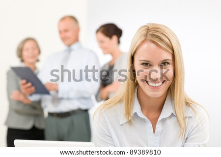 Business team attractive woman with happy colleagues discussing in back - stock photo