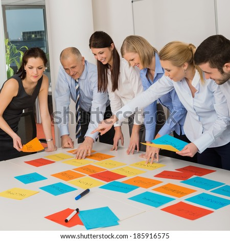 Business team brainstorming using color labels on table in office - stock photo