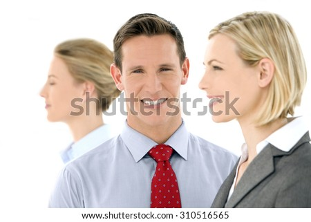 Business Team. Business people standing in a row. Selective focus on the man, who is looking at camera, Two others looking away. Profile view. - stock photo