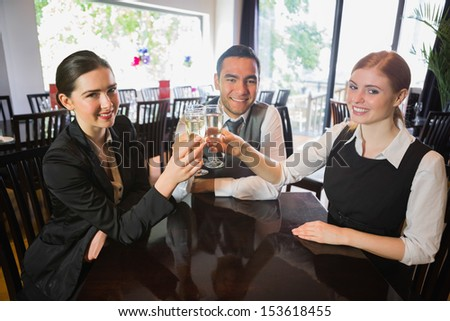 Business team celebrating a success with champagne in restaurant looking at camera