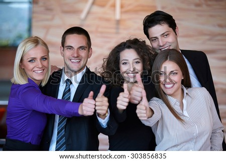Business team celebrating a triumph in office with arms up - stock photo