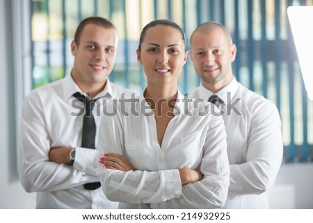 Business team celebrating a triumph with arms up in office - stock photo