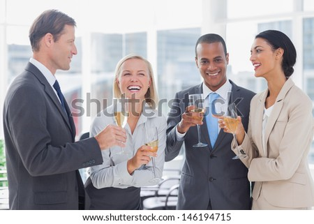 Business team celebrating with champagne in the office - stock photo