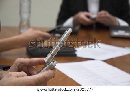 Business team check their phones during a meeting.