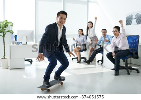 Business team cheering their chief on skateboard