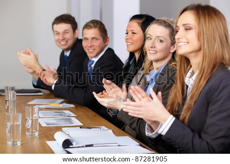 Business team clapping hands during their meeting, focus on blonde smiling female - stock photo