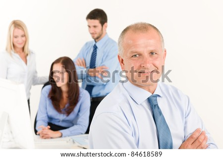 Business team close-up of senior businessman with attractive happy colleagues