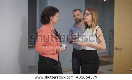 Business Team Coffee Break Relax Concept. Business people colleagues communicate in an informal setting, laughing. Taken in an office corridor - stock photo
