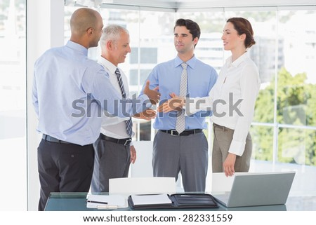 Business team congratulating their colleague in the office - stock photo