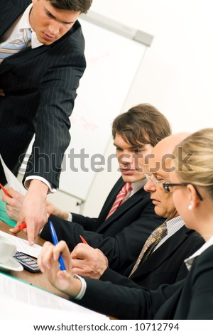 Business Team discussing documents, presumably contracts or numbers - stock photo