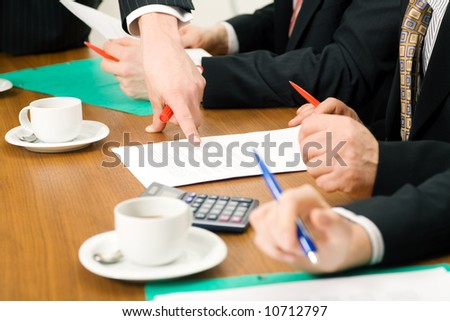 Business Team discussing documents, presumably contracts or numbers, closeup - stock photo