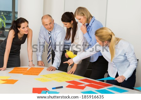Business team discussing multicolored labels in boardroom meeting - stock photo