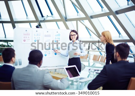 Business team discussing new charts at conference - stock photo