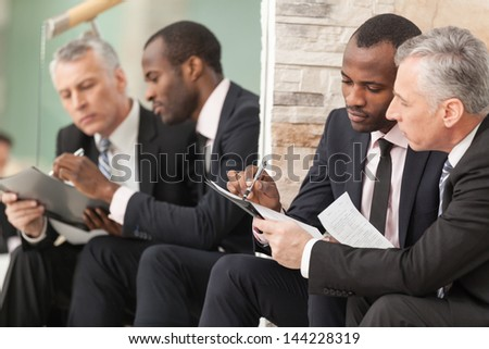 Business team discussing papers on staircase