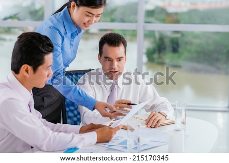 Business team discussing report - stock photo