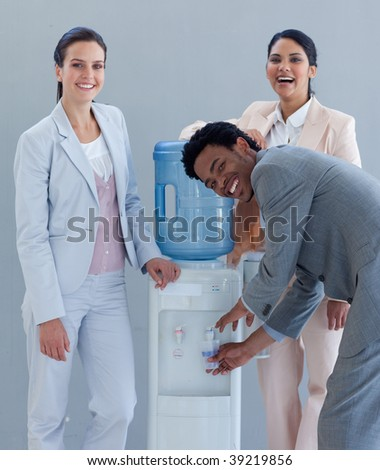 Business team drinking from a water cooler in office - stock photo