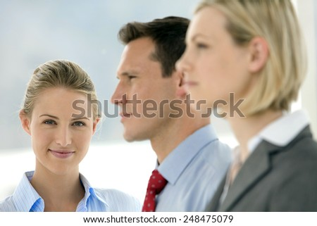 Business team - Focus on businesswoman looking at camera - other executives looking away - stock photo