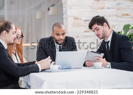 Business team. Four smiling successful businessmen at a meeting while sitting at a table discussing business affairs in the office