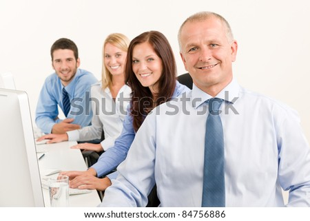 Business team handsome mature manager sitting behind computer table office
