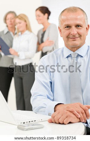 Business team happy mature businessman with attractive colleagues looking file - stock photo