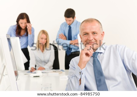 Business team happy mature businessman with attractive colleagues looking files