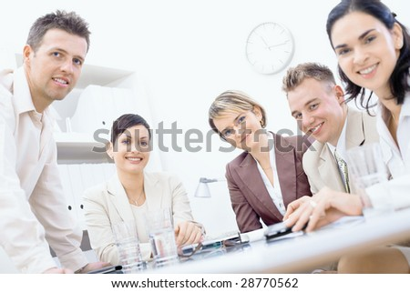 Business team having a meeting. Businessman leaning on desk, others sitting around, looking at camera, smiling. - stock photo