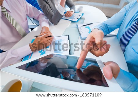 Business team having roundtable discussion at the office viewed below - stock photo