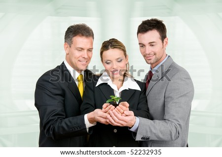 Business team holding a fresh new plant on palm in modern office. Symbol of green, new and growing business - stock photo