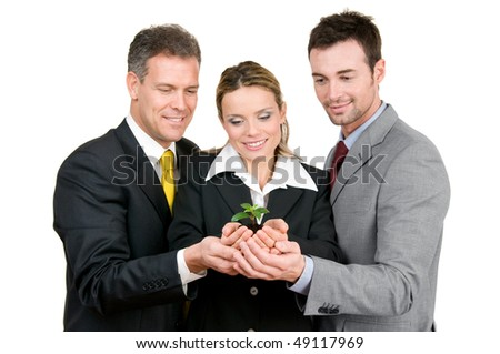 Business team holding a fresh new plant on palm, symbol of green, new and growing business