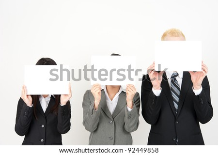 business team holding a whiteboard hiding their face - stock photo