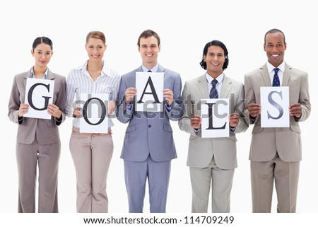 Business team holding the letters of GOALS against white background - stock photo