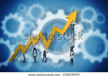 Business team holding up arrow against white wheels and cogs on blue - stock photo