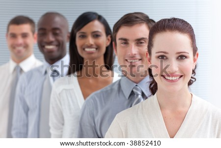 Business team in a line smiling at the camera. Focus on a beautiful woman