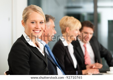 Business - team in an office; a woman is looking into the camera - stock photo