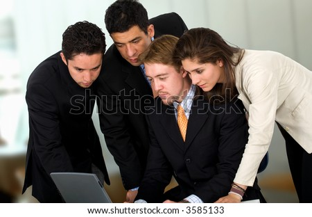 Business team in an office environment all wokring on a laptop computer - stock photo