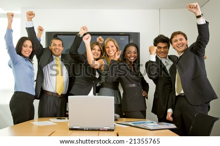business team in an office full of success looking happy - stock photo