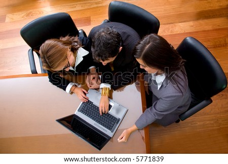 business team in an office laptop computer - meeting taken from the top at a very high angle - stock photo