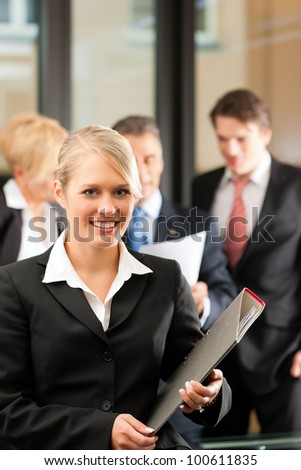 Business - team in an office, the junior manager is standing in front - stock photo