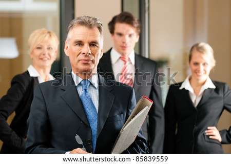 Business - team in an office; the senior executive is standing in front - stock photo