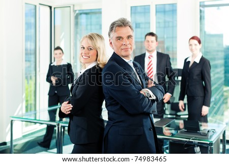 Business - team in an office; the senior executive is standing in front with his secretary